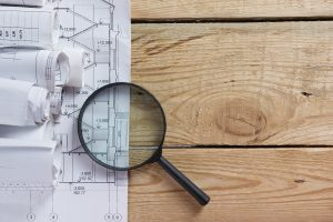 Architectural blueprints, blueprint rolls magnifying glass near checkered blank paper with pen on vintage wooden background. Construction concept. Architect workplace top view. Copy space